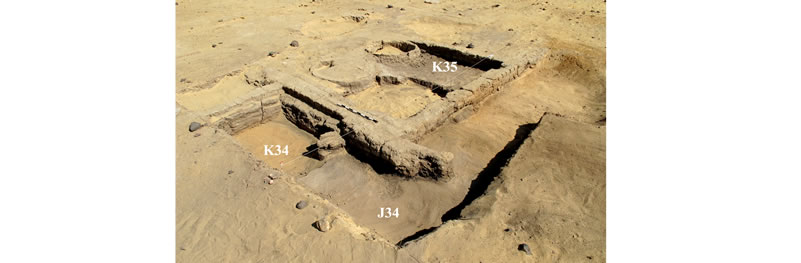 Figure 5 View (looking northwest) of Structure A, the 4m x 4m squares are labeled in their southeast corners. Inside Room I, the clean sand that underlies Level 3 is visible in Square K34 (and the western portion of J34), while the top of Level 3 (the ash and debris that accumulated prior to the construction of Structure A) is visible in Square K35 (and the western portion of J34).